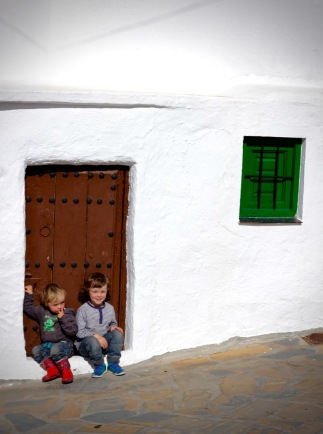Sitting on the doorstep of a whitewashed house, Comares, Andalucia